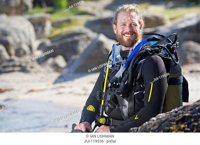 Man in wetsuit going ocean scuba diving from rocky beach and smiling at camera