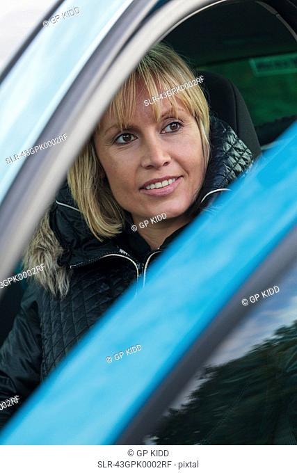 Smiling woman opening car door