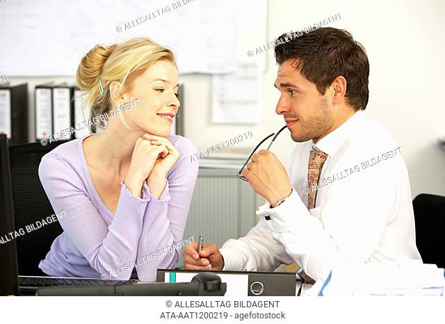 Young couple flirting in the office