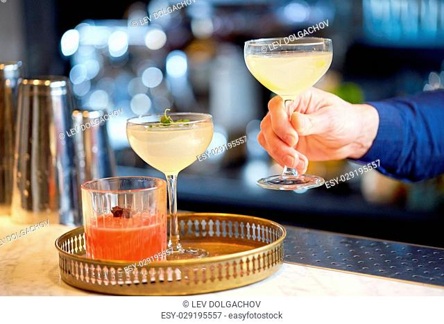 alcohol drinks, people and luxury concept - bartender putting glasses of cocktails to tray at bar