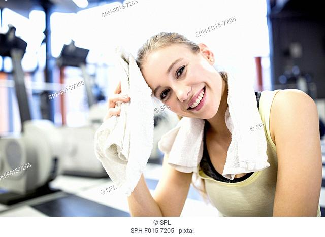 MODEL RELEASED. Young woman wiping her sweat with towel after exercising in gym