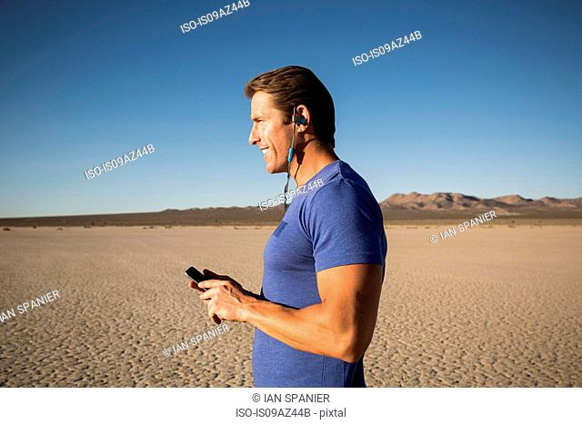 Man training, listening to bluetooth headset on dry lake bed, El Mirage, California, USA