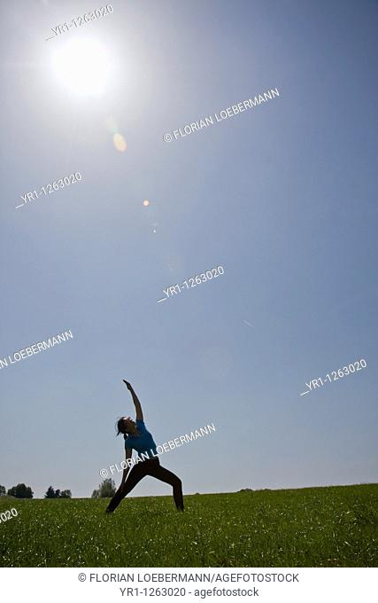 Asian girl doing yoga workout on a field during summer. Shot in Aachen, Germany