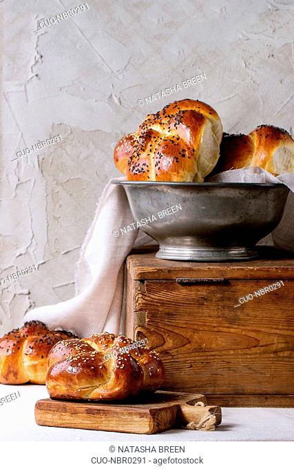 Heap of sweet round sabbath challah bread with white and black sesame seeds in vintage metal bowl on wooden chest and on small cutting board over white table...