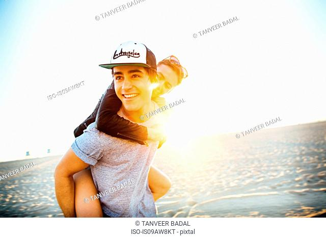 Young man giving girlfriend a piggy back on sunlit beach, Venice Beach, California, USA