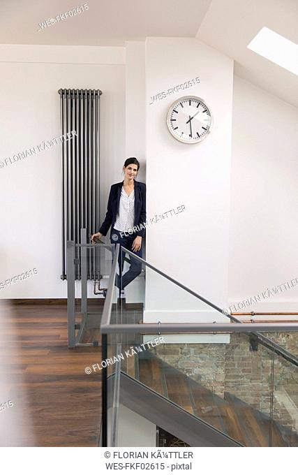 Businesswoman leaning against wall in office, waiting under clock