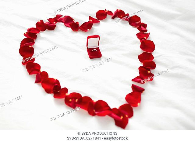 heart made of petals and diamond ring in gift box