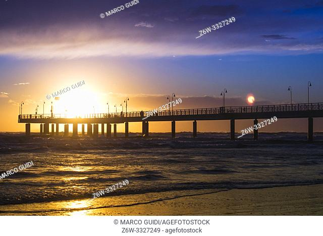 The pier of Marina di Pietrasanta taken on a windy day at sunset