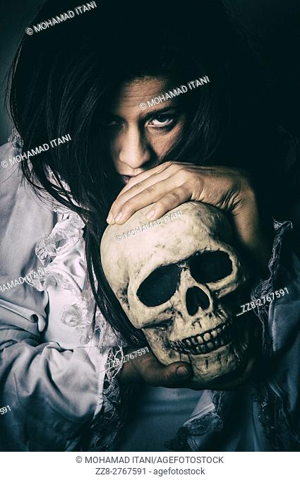 Frightened woman holding a skull