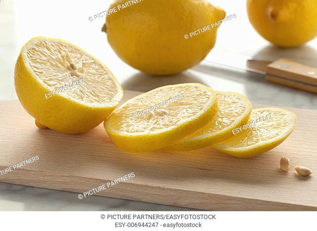 Fresh lemons and slices on a cutting board
