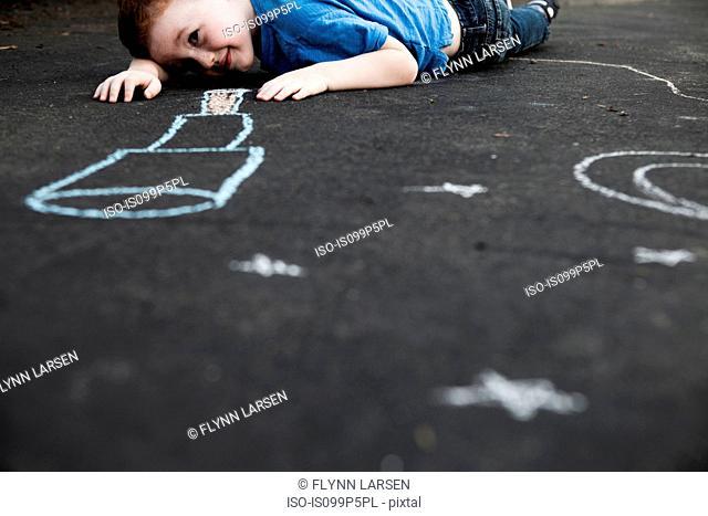 Boy lying on floor looking at chalk drawing