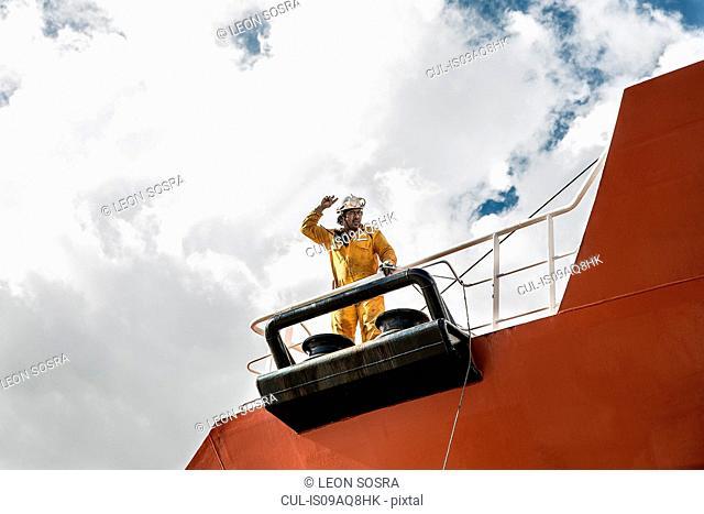 Worker mooring oil tanker on deck making hand gesture