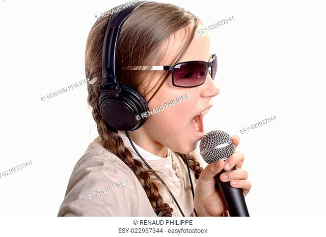 a young girl with headphones singing with a microphone