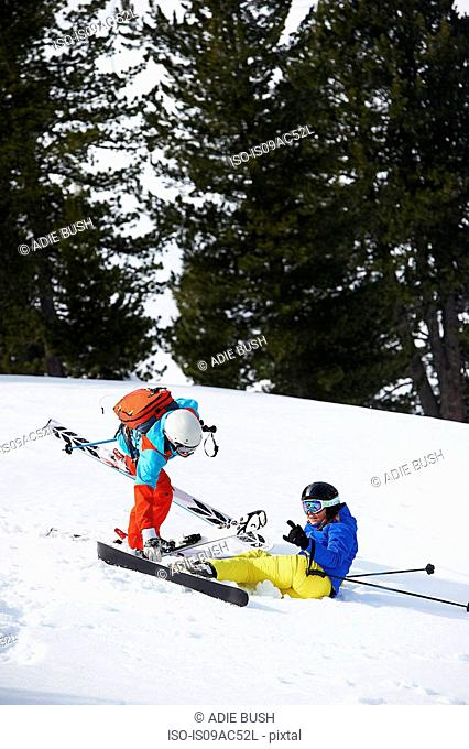 Skier helping another up
