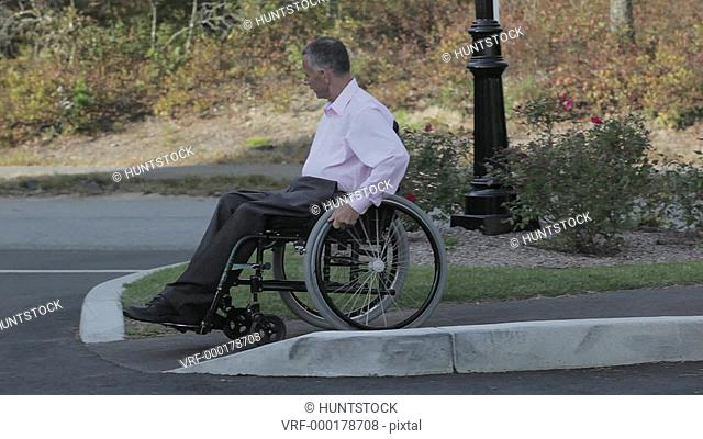 Man with spinal cord injury in a wheelchair using accessible sidewalk to street ramp