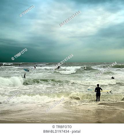 People surfing in stormy ocean