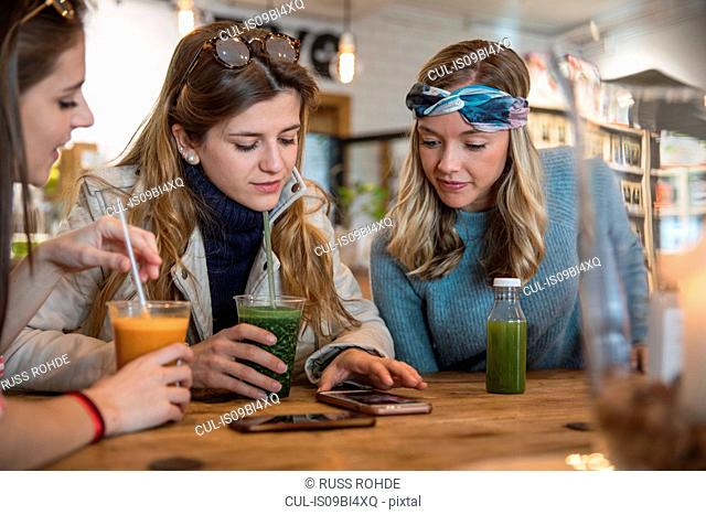 Three female friends, sitting in cafe, drinking smoothies, laughing