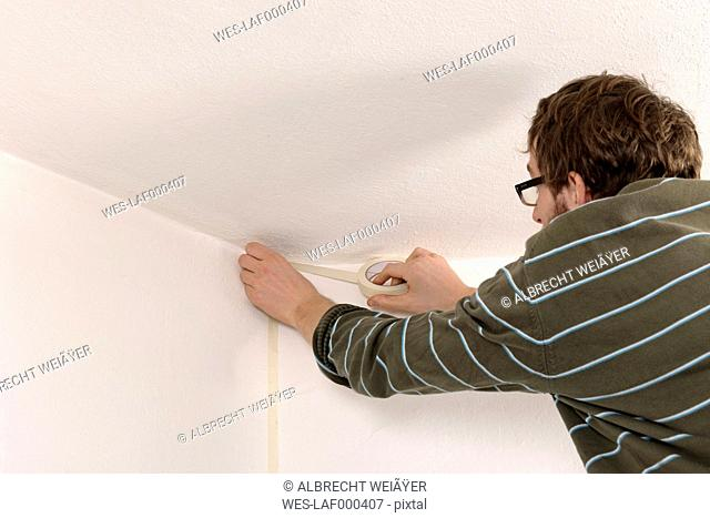 Young man masking wall with adhesive tape