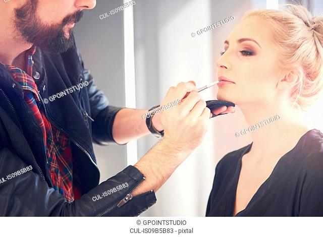 Male make up artist applying lipstick to model for photo shoot