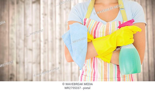 Woman in apron with cleaner against blurry wood panel
