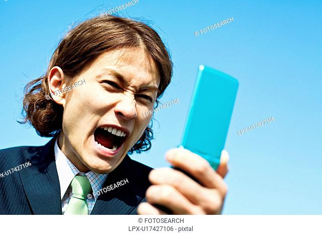 Businessman Shouting to Mobile Phone
