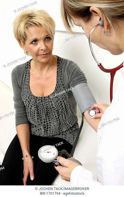 Medical practice, medical technician taking the blood pressure of a patient