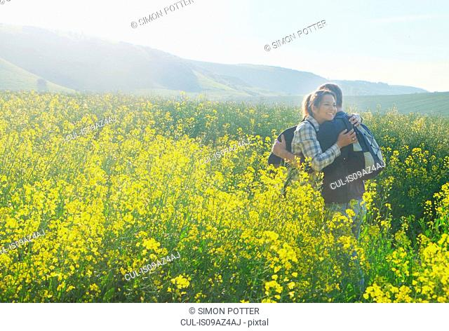 Couple in rapeseed field hugging