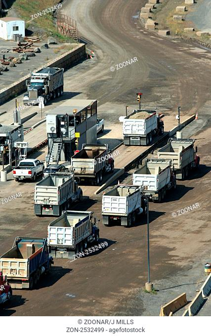 A bunch of Dump trucks lined up at a rock quarry