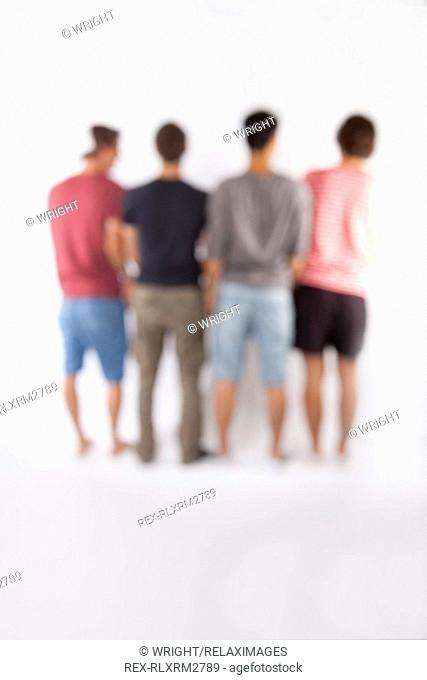 Teenagers four male boys rear view group 4 blurred