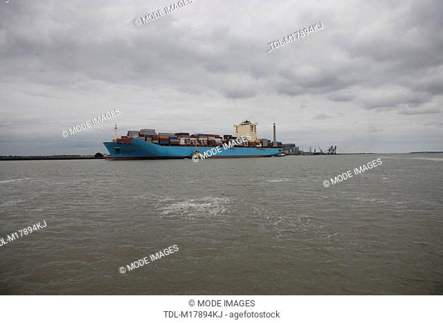 A container ship escorted by tug boats