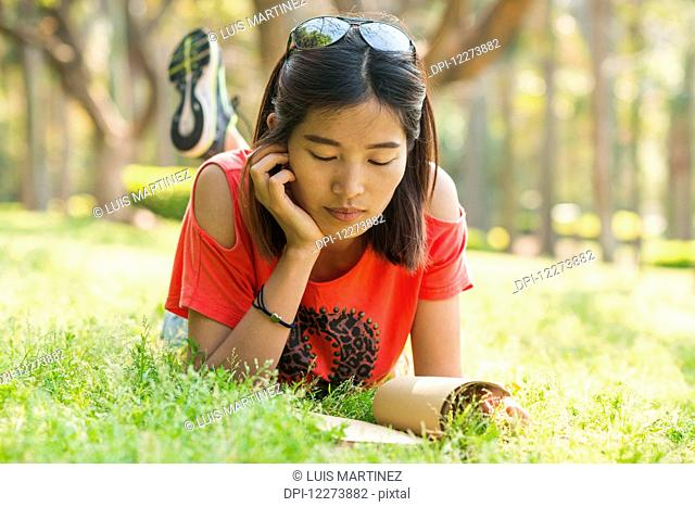Chinese girl reading a book on the grass; Xiamen, Fujian Province, China