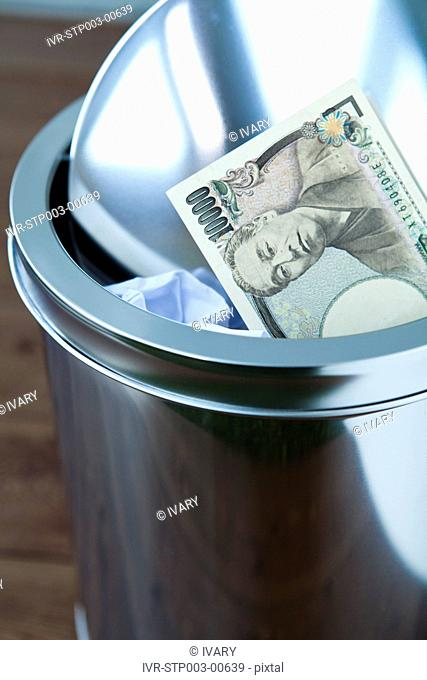 Close-up Of Dustbin And Currency