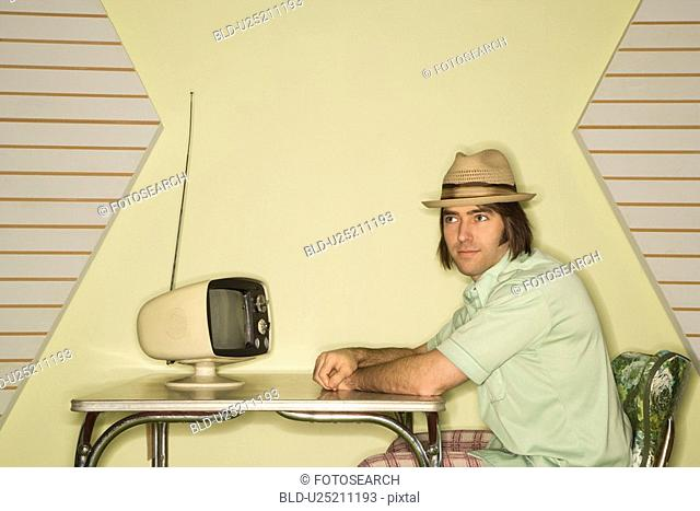 Caucasian mid-adult man wearing hat sitting at 50's retro dinette set in front of old television