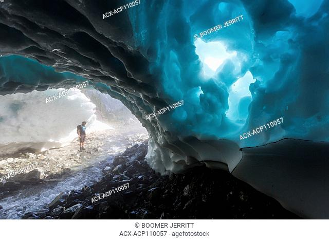 A hiker walks through a snow cave at the base of Century Sam lake, Strathcona Park, Vancouver Island, British Columbia, Canada