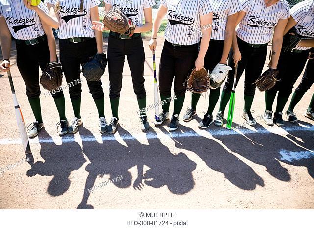 Middle school girl softball team standing in a row behind line on baseball diamond