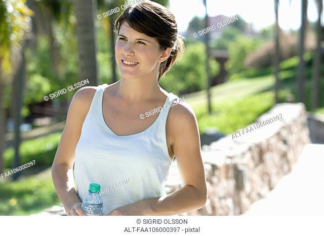 Woman walking in park with water bottle
