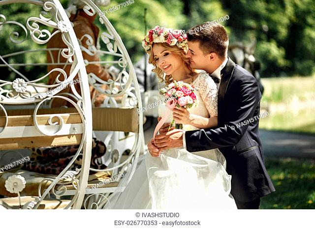 Romantic fairy-tale wedding couple bride and groom hugging in magical cinderella white carriage