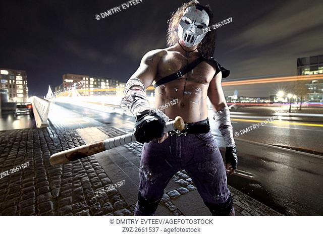 Costumed hero as a street maniac with a bat. Casey Jones on Copenhagen street. Combined image - studio work was added to real landscape