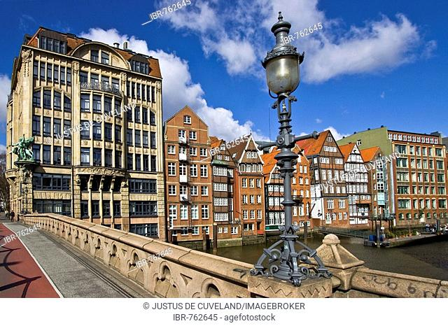 Bridge with ornate lamps leading to Haus der Seefahrt (House of Seafaring) at left beside historic timber-framed merchant houses on the Nikolaifleet in the...