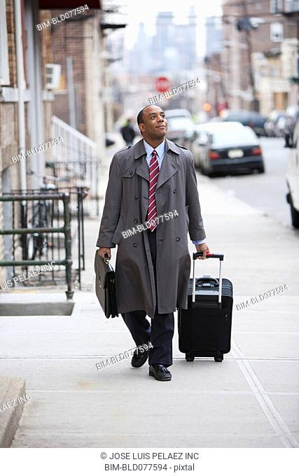 African businessman pulling suitcase