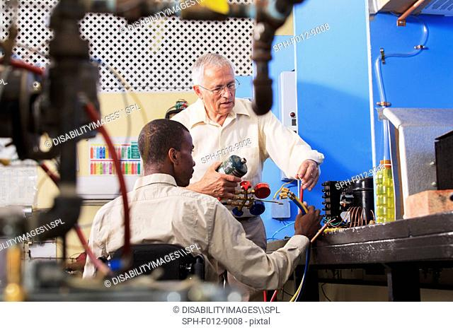 Instructor demonstrating air conditioner recharging manifold with gauges in HVAC classroom student in wheelchair