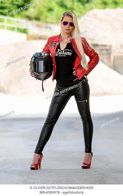 Young woman with long blonde hair poses posing with motorcycle helmet and sunglasses