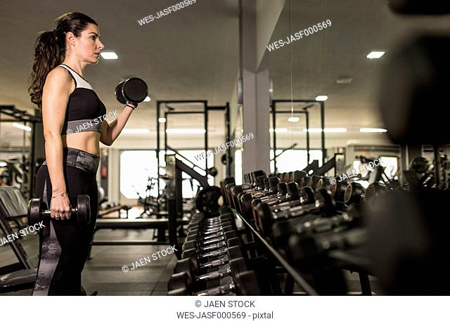 Mature woman training biceps, lifting dumbbells in gym