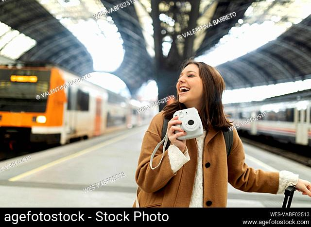 Happy young woman with camera at the train station