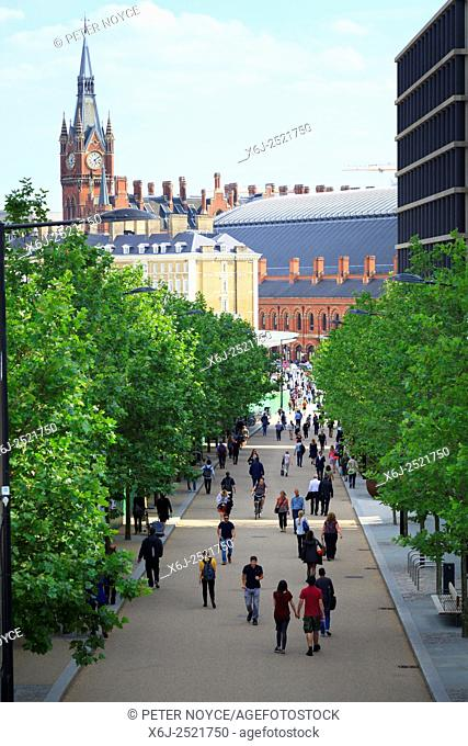 People walking along King's Boulevard with the St Pancras Clock Tower