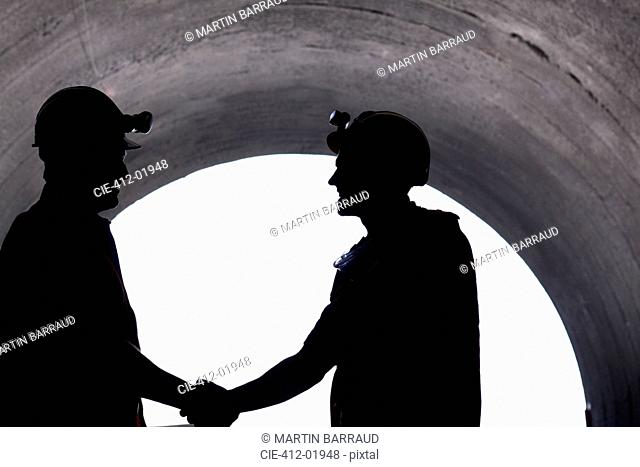 Silhouette of workers shaking hands in tunnel
