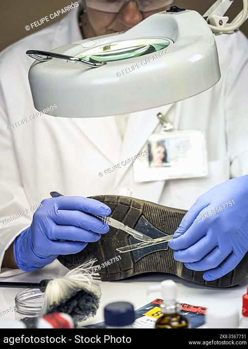Specializing police officer analyzes ground in a victim's shoe murder with one tweezers, conceptual image