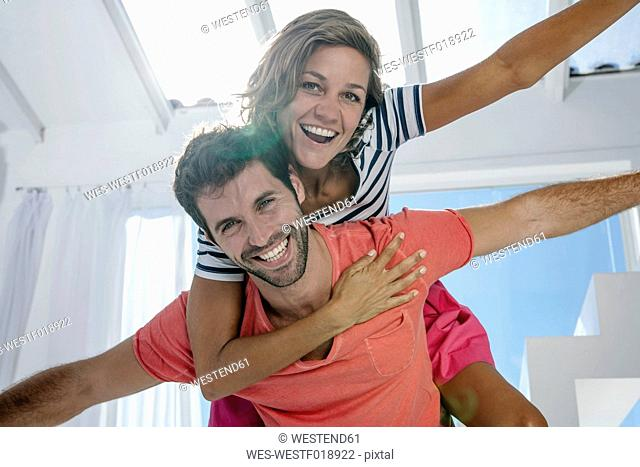 Spain, Mid adult man giving piggy back ride to woman, smiling