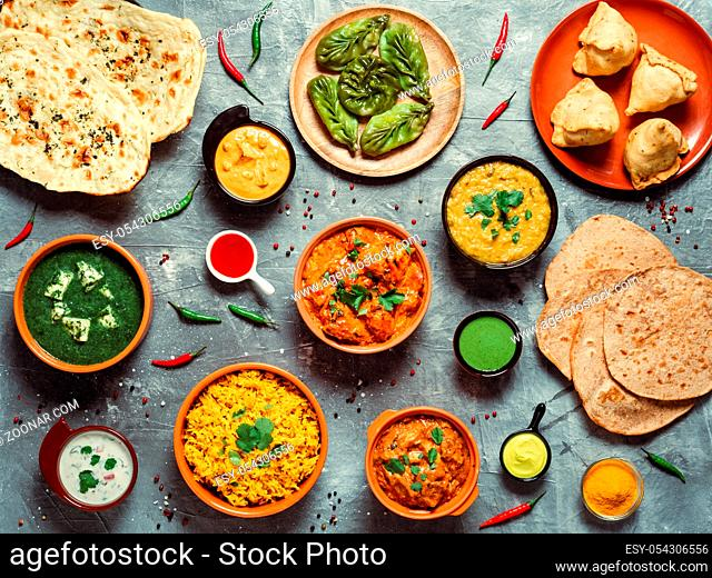 Indian cuisine dishes: tikka masala, dal, paneer, samosa, chapati, chutney, spices. Indian food on gray background. Assortment indian meal top view or flat lay