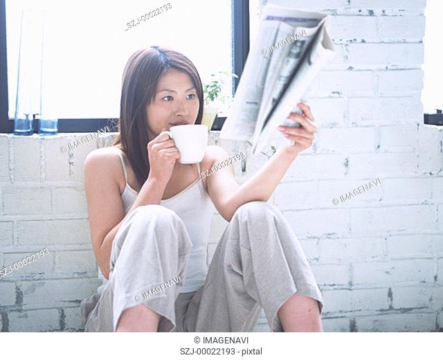 Woman reading newspaper on floor